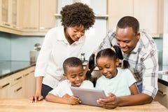 使用片剂的愉快的家庭在厨房里 免版税库存图片