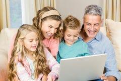 使用膝上型计算机的愉快的家庭在沙发 免版税库存图片