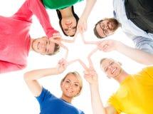 站立五颜六色的衣物的愉快的学生一起做与他们的手指的一个星 免版税图库摄影