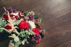 与红色玫瑰和丁香的土气婚礼花束在木开花 库存照片