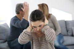 战斗在小女孩前面的父母 免版税库存照片