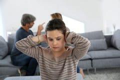 战斗在他们的女儿前面的父母 免版税库存图片