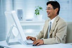 使用他的计算机的微笑的商人 库存照片
