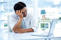 看他的膝上型计算机的疲乏的亚洲商人 免版税库存图片