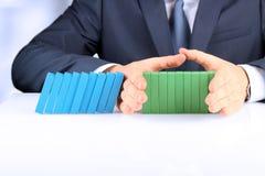 Планирование, риск и стратегия в деле, бизнесмене держа деревянные блоки Бизнесмен останавливая влияние домино Стоковое Фото