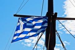 在爱琴海附近希腊海岸航行的船的希腊旗子 免版税库存照片