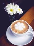 有戴西花装饰的咖啡杯在木桌上 库存图片