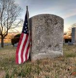 一个军事退伍军人的破旧的墓碑尊敬与一面美国国旗 免版税图库摄影
