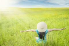 无忧无虑的妇女享受绿色草甸视图 库存照片