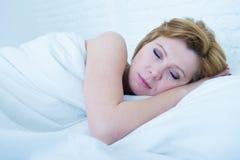 有红色头发的在家平安地睡觉在床上的年轻可爱的妇女的面孔休息和作梦 免版税库存照片
