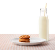 在白色板材和瓶的花生酱曲奇饼牛奶 库存照片