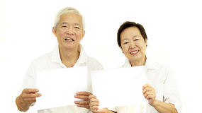 拿着白色空白的标志的愉快的亚洲资深夫妇准备好赞成 免版税库存照片