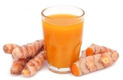 与萃取物的新鲜的姜黄在玻璃 库存照片