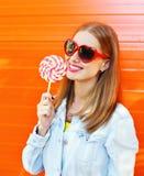 太阳镜的愉快的微笑的妇女有在五颜六色的橙色背景的甜棒棒糖的 免版税图库摄影