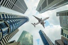Ψηλά κτήρια πόλεων και ένα αεροπλάνο που πετά από πάνω το πρωί Στοκ εικόνα με δικαίωμα ελεύθερης χρήσης