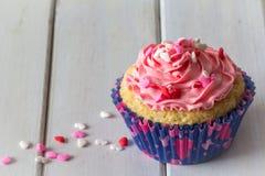 唯一杯形蛋糕和桃红色结霜在表上与拷贝空间在垂直上 免版税库存图片