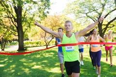 Счастливый молодой мужской бегун выигрывая на отделке гонки Стоковая Фотография RF