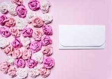 在一个桃红色背景五颜六色的纸玫瑰装饰情人节边界的白色信封,地方文本顶视图克洛 免版税图库摄影