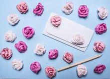 在蓝色背景的白色信封与五颜六色的纸玫瑰和铅笔顶视图关闭 免版税库存照片