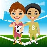 两位逗人喜爱的多种族青年足球运动员 免版税库存照片