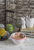 与一个篮子的舒适家庭位子与毛线、被堆积的书、花瓶有干燥分支的,一只陶瓷兔子和一杯奶茶 图库摄影