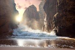 大岩石和海浪在日落 免版税库存图片