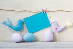 复活节彩蛋和两只鸟在淡色与一张空白的蓝色卡片在白色木背景 库存照片