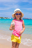 吃在夏天海滩背景的愉快的小女孩冰淇凌 免版税库存照片