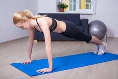 Νέα όμορφη γυναίκα που κάνει την ώθηση επάνω στην άσκηση στο σπίτι Στοκ Εικόνα