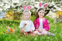 使用用复活节彩蛋的两个可爱的妹在复活节天 图库摄影