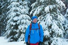 站立在冬天森林里的愉快的远足者人 免版税库存照片