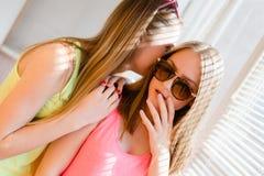 有两个美丽的白肤金发的十几岁的女孩乐趣愉快微笑 库存照片