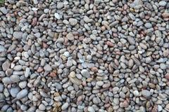 湿小卵石向抽象背景扔石头 免版税库存照片