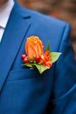 橙色玫瑰钮扣眼上插的花在他的夹克男性的口袋的 免版税库存图片