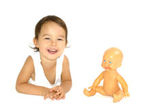 Маленькая девочка играя с ее куклой в студии изолировано Стоковые Фото