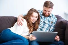 使用便携式计算机的愉快的夫妇在沙发 库存图片