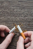 打破香烟的男性手 免版税库存图片