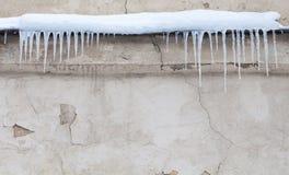 在屋顶的冰柱 葡萄酒破旧的墙壁背景 冷的冬天天气概念 软绵绵地集中 免版税库存图片