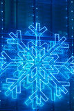 Τα Χριστούγεννα ανάβουν τη διακόσμηση σε μια πρόσοψη οικοδόμησης στον μπλε τόνο Στοκ Φωτογραφία