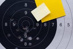特写镜头黄色便条纸板料 在黑白一个射击纸目标和靶心与弹孔 免版税库存照片