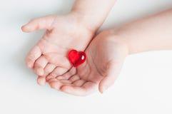 红色心脏在婴孩的手上 免版税库存照片