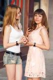 两个快乐的女孩立场和互相讲话 图库摄影