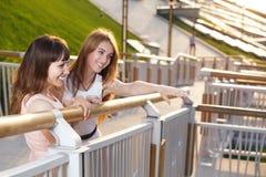 两个在台阶的快乐的女孩立场 免版税图库摄影