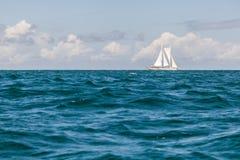 在天际的孤立帆船在热带水 免版税图库摄影