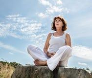 呼吸户外为美好的中部变老了瑜伽妇女 库存图片