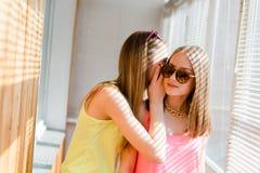 有两个美丽的白肤金发的十几岁的女孩乐趣愉快微笑 免版税图库摄影