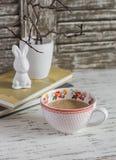杯奶茶、书和一只陶瓷兔子在轻的木桌上 库存照片