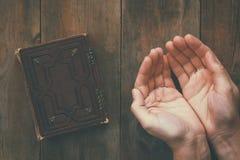 顶视图图象人在祷告折叠的手在祈祷书旁边 宗教、灵性和信念的概念 免版税库存图片