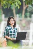 使用膝上型计算机的年轻亚裔妇女,当坐公园时 免版税库存图片