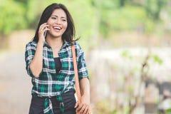 年轻亚裔妇女说在电话里,当走在同水准时 免版税图库摄影